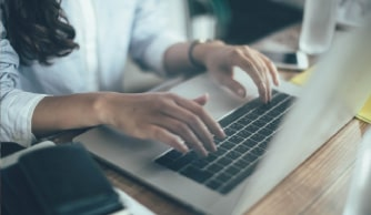 ノートパソコンで作業する女性の手元
